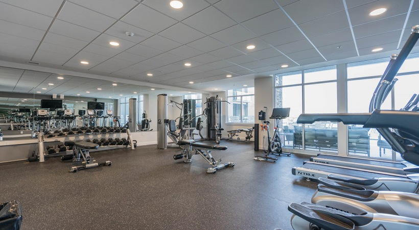 brightly lit fitness center with floor-to-ceiling windows